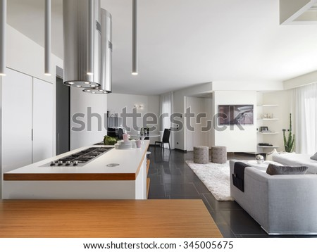internal view of a modern kitchen  overlooking on the living room and the entrance - stock photo