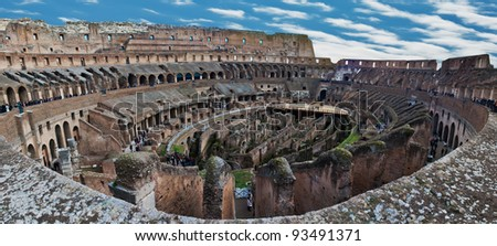 Internal wide angle view of Roman Colosseum (Flavian Amphitheatre) showing passages under the arena, the corridors, the stands and the outer walls. Tourists milling around the walkways and terraces. - stock photo