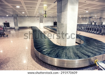 International airport baggage claim area, suitcases on carousel at local terminal - stock photo