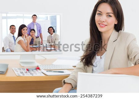 International business associates in a meeting against female artist sitting at desk with computer in office - stock photo