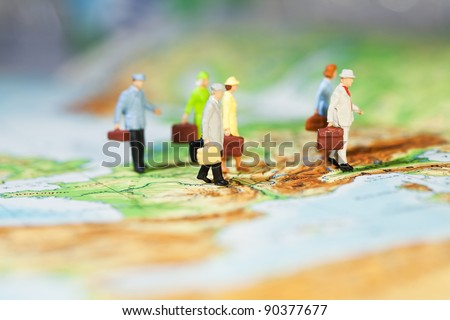 International Business Cooperation, a groupd of miniature businesspeople models walking across a map, low angle and shallw DOF. - stock photo