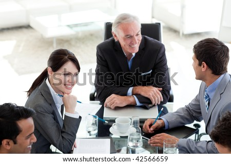 International business people discussing a business plan sitting around a conference table - stock photo