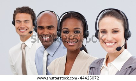 International business people with headset on in a line smiling at the camera