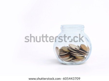 International coins in a glass jar on white background with copy space.