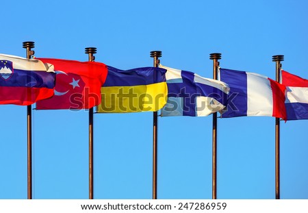 International colored flags at blue sky.  State flags of Slovenia, Turkey, Ukraine, Finland, France and the Netherlands. Flags of European countries on the flagpole waving in the wind. - stock photo