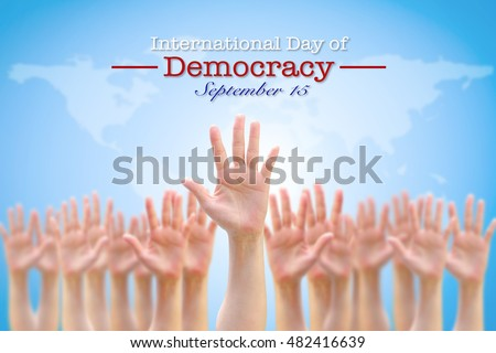 International day of democracy, September 15: Observance to raise public awareness on importance of democratic rights society: Many human people hands raising up in air with world map background