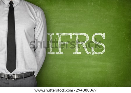 International financial reporting standards on green blackboard with businessman on side - stock photo