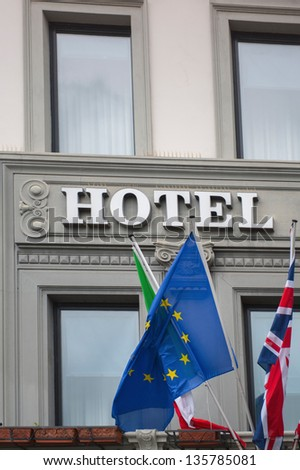 International hotel sign with European Union, United Kingdom and Italian flag. - stock photo