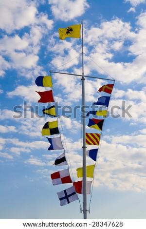 international maritime signal flags against a blue sky - stock photo