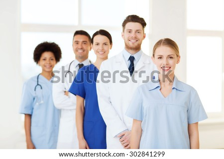 international, profession, people and medicine concept - group of happy doctors and nurses at hospital