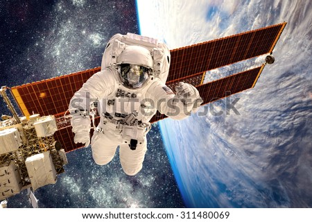 International Space Station and astronaut in outer space over the planet Earth. Elements of this image furnished by NASA. - stock photo