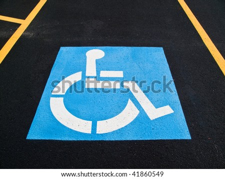 International Symbol of Access ,Handicap parking sign painted in a black asphalt parking lot bordered by two yellow parking space guide lines - stock photo