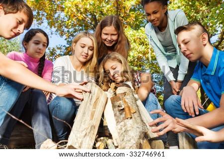 International teens construct bonfire together - stock photo