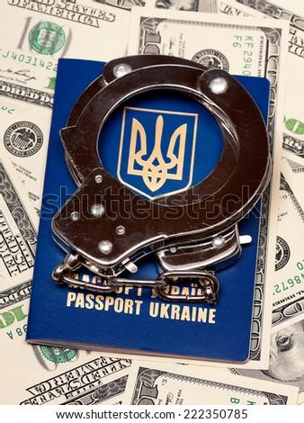 International Ukrainian passport with handcuffs on US dollars background - stock photo