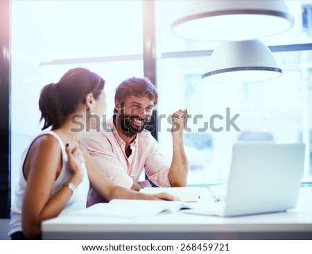 International university students working with laptop on a project while sitting in the study hall,couple of young designers or coworkers working at modern office while discussing things of work,flare - stock photo