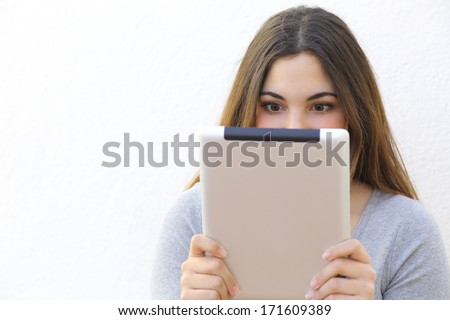 Internet addiction woman reading a tablet reader on a white wall background - stock photo