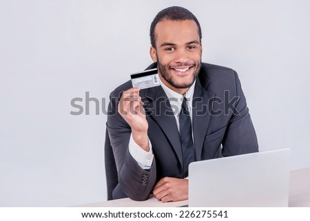 Internet banking sales. Successful African businessman sitting at a laptop and holding credit card in hand until businessman doing orders through the Internet - stock photo
