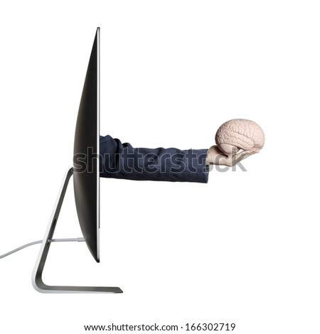 Internet education, Hand holding a human brain extending out from a computer screen  - stock photo