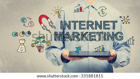 Internet Marketing concept with young man holding a tablet computer  - stock photo