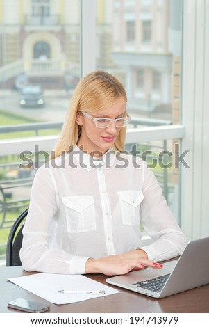 Internet meeting. Businesswoman in glasses holding a pen near the head and thinking about work and looking in the camera. Beautiful blonde woman. - stock photo