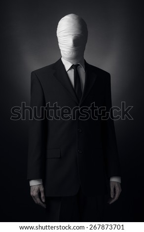 Internet meme and terrible character Halloween theme: very tall burly man with long arms in a suit with bandaged face fabric, an unknown killer in the suit, The Slender Man, Secret legend of the city - stock photo