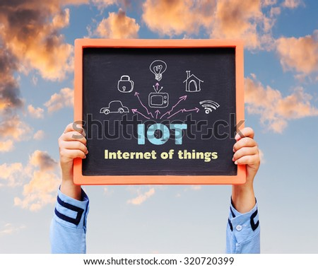 Internet of Things (IoT) word with icon on blackboard. - stock photo