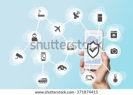 Internet of things security concept with hand holding modern smart phone to control intruders into a network of objects - stock photo