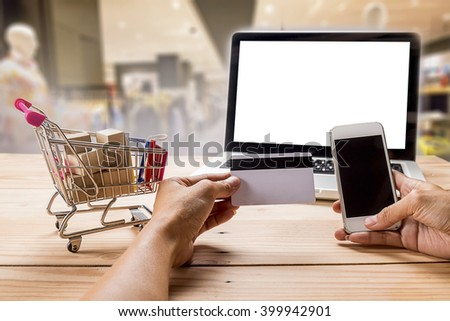 Internet online shopping concept with colourful paper shopping bags and shopping-cart.Vintage tone retro filter effect,soft focus(selective focus) - stock photo