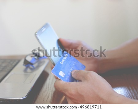 internet online shopping concept with credit card, shopping cart and blurred young man using tablet in background