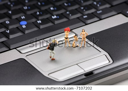 Internet pornography concept. Miniature nude models pose on a laptop with a photographer taking their picture. - stock photo
