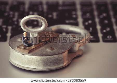 Internet security concept-miniature businessman stand on old key and padlock on laptop computer keyboard - stock photo
