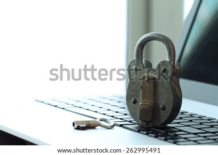 Internet security concept-old  padlock and key on laptop computer keyboard - stock photo