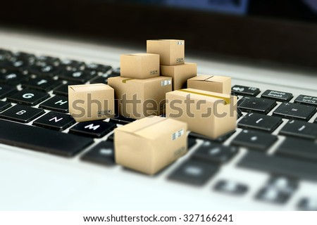 Internet shopping, merchandise cardboard boxes on laptop keyboard - stock photo