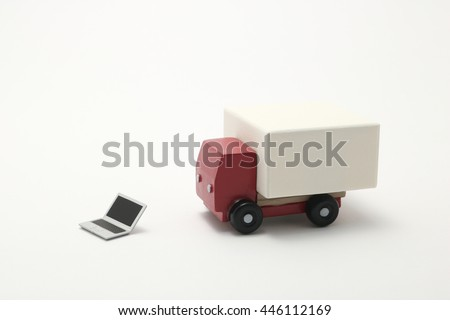 Internet shopping, on line purchase, e-commerce and packages delivery concept.   Toy car truck and miniature laptop on white background. - stock photo