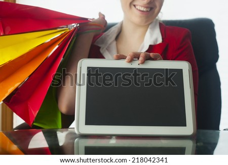 Internet shopping online: Smiling woman with tablet pc and bags - stock photo