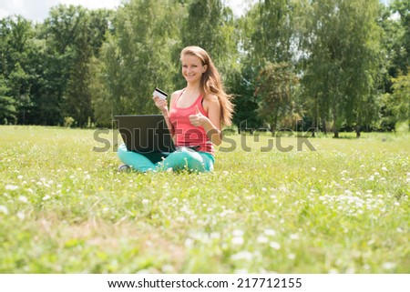 Internet shopping woman online with laptop and credit card sitting outdoor on green grass. Happy internet shopper with thumb up buying things on the internet.