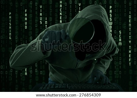 Internet Theft - a hooded man looking at computer screen using magnifying glass  - stock photo
