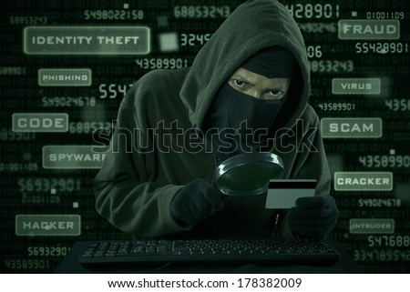 Internet Theft - a man wearing a balaclava looking at credit card code using magnifying glass - stock photo