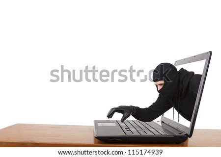 Internet theft  - a man wearing a balaclava reaching out through a laptop screen onto the keyboard. - stock photo