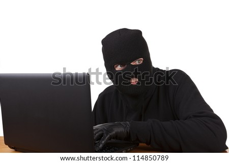 Internet Theft - a man wearing a balaclava sat behind a laptop, white background.