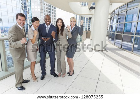 Interracial business team, men & women, businessmen & businesswomen, using tablet computer and celebrating success on a city rooftop - stock photo