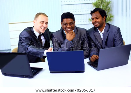 Interracial business team working at laptop in a modern office - stock photo