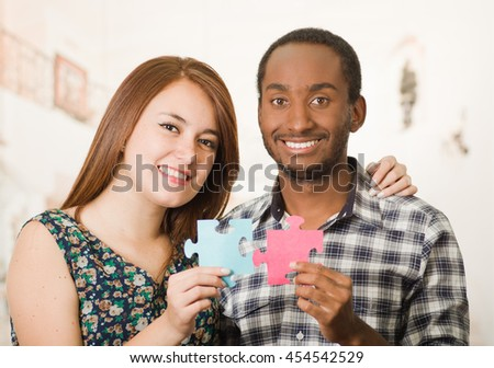 Interracial charming couple embracing friendly, holding up large puzzle pieces and happily interacting having fun, blurry studio background - stock photo