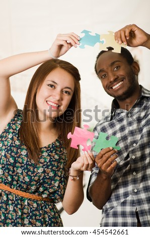Interracial charming couple wearing casual clothes holding up large puzzle pieces and interacting happily, white studio background - stock photo