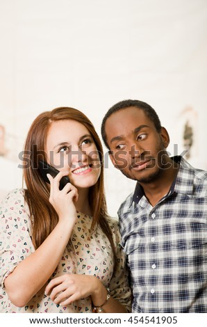 Interracial charming couple wearing casual clothes posing interacting friendly, woman talking on cell phone and man listening in, white studio background - stock photo