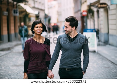 Interracial couple holding hands on the street - stock photo