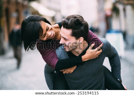 Interracial couple in love having fun in the city - stock photo