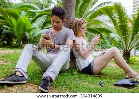 Interracial Couple Lovers Sitting On The Grass With Mobile In Their Hands - stock photo