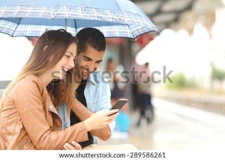 Interracial couple sharing a phone in a train station while wait under an umbrella in a rainy day - stock photo