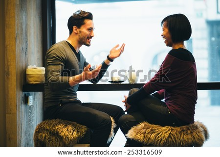 Interracial couple talking in coffee shop - stock photo